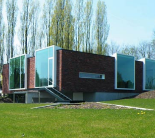 AtelierVensVanbelle衣着的办公室扩建部分提供砖砌和树木的倒影